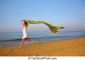 Young girl runs on edge of sea with yellow fabric shawl in hands