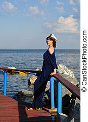 Young girl sailor walking on the pier and waiting for his ship in the summer