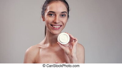 Young Girl Showing Cream in Jar