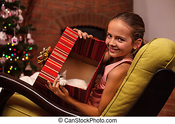 Young girl showing her christmas present in a large box - a cute kitten