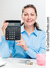 Young girl shows on the calculator the earned amount of money