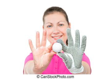 Young girl shows the ball for the game of golf on a white background
