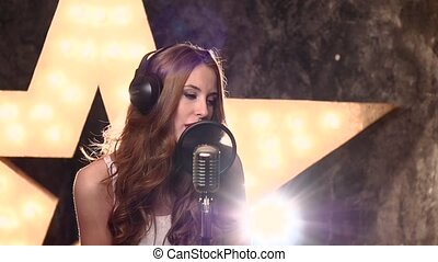 young girl singer recording a song in music studio,slow motion, close up