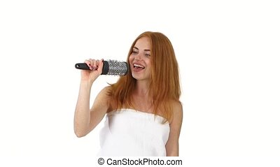 Young girl singing using a brush as a microphone, slow motion, bathroom