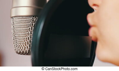 Young girl sings something in a studio microphone at a...