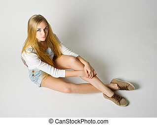 Young girl sit on the floor on grey