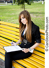 young girl sits in park on a bench