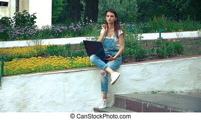 young girl sits near the flowerbeds with colors and prints on a laptop