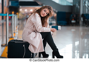 Young girl sits on a suitcase in airport.