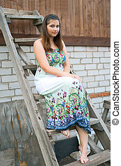 girl sits on a wooden ladder