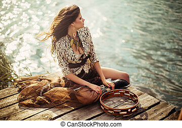 young girl sits on the riverside - beautiful young girl sits...