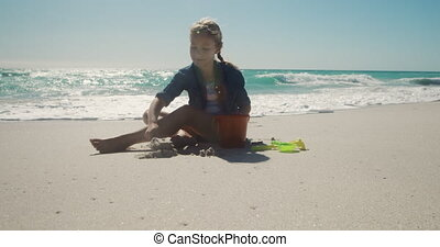 Young girl sitting and playing with the sand