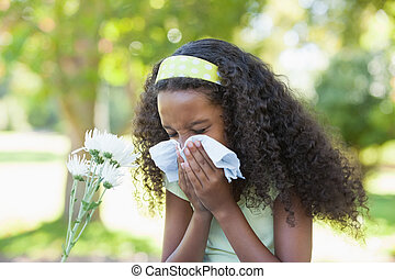 Young girl sitting by flower and blowing her nose in the park