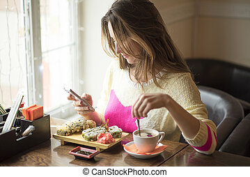 Young girl, sitting cafe with cup coffee and read messages...