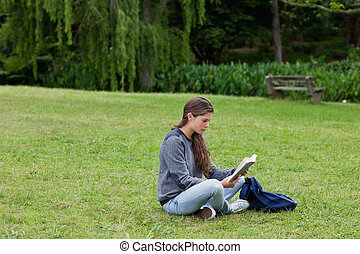 Young girl sitting cross-legged while reading a book