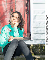 Young Girl Sitting Down Writing In Notepad
