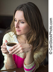Young girl, sitting in a cafe with cup of coffee