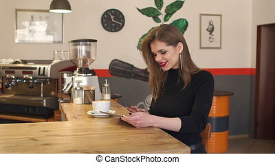 Young girl sitting in a coffee shop with a Cup of coffee and a tablet.