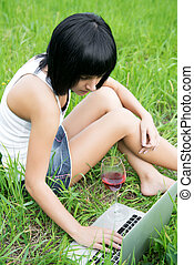 Young girl sitting in a park with laptop computer