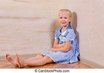 Young girl sitting in corner
