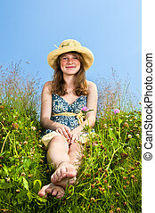 Young girl sitting in meadow