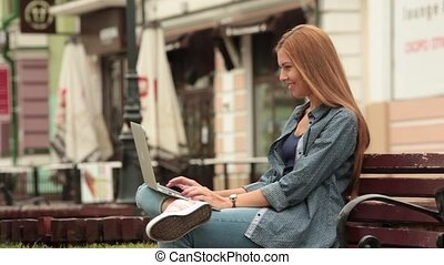 Young girl sitting on a bench in the city and working on a laptop.