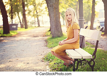 Young Girl Sitting on a Bench