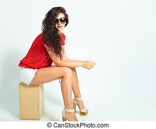young girl sitting on a chair in studio with hands on her knees while wearing sunglasses