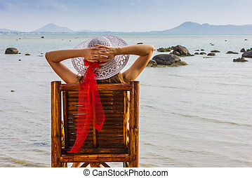 young girl sitting on a chair near the sea