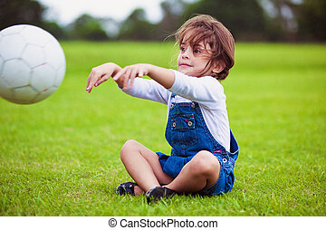 Young girl sitting on a grass throwing ball