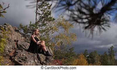 young girl sitting on a hill