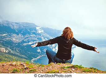 young girl sitting on a hill overlooking the sea and mountains a