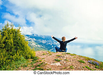 young girl sitting on a hill overlooking the sea and mountains w