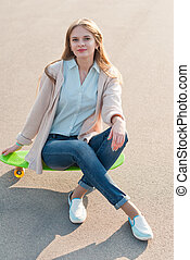 Young girl sitting on a skateboard in the street.