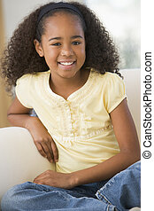 Young Girl Sitting On A Sofa At Home