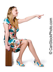 Young girl sitting on a suitcase and shows the side with your finger. Isolated on white background
