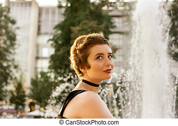 Young girl sitting on a sultry hot summer day near the fountain