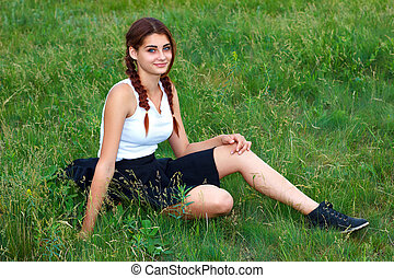 young girl sitting on green grass