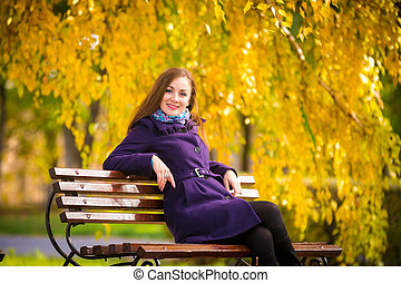 Young girl sitting on the bench warm autumn day