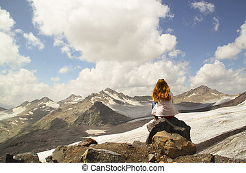 Young girl sitting on the edge of a cliff and looking at the sky