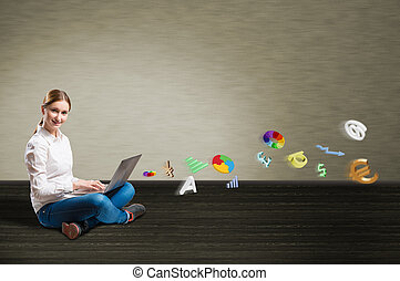 young girl sitting on the floor with a laptop