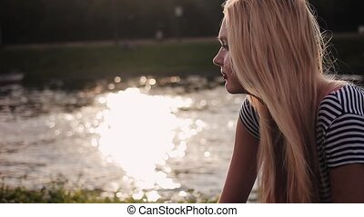 Young girl sitting on the gren grass near the river at sunset