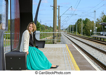 Young girl sitting on the railway station