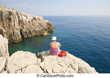 young girl sitting on the rock