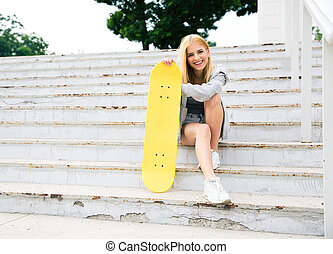 Young girl sitting on the stairs with skateboard