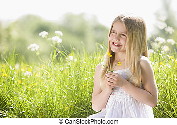 Young girl sitting outdoors holding flower smiling