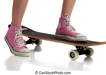 Young girl skateboarding with pink sneakers - A young girl ...
