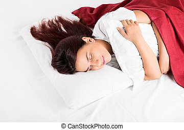 Young girl sleeping on a bed hugging a pillow