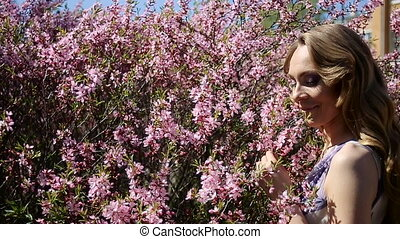 young girl smelling a pink little flowers