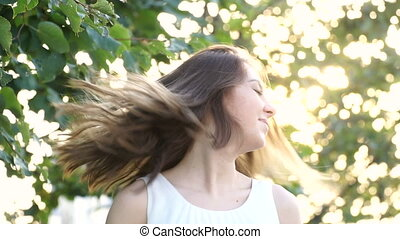 young girl smiling twists head and her hair fly away in slow...